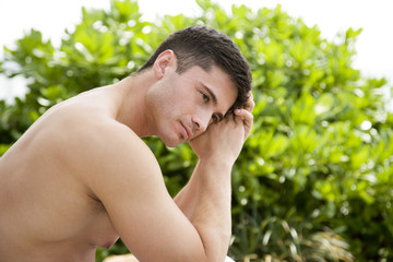 Topless man sitting outside, looking thoughtful