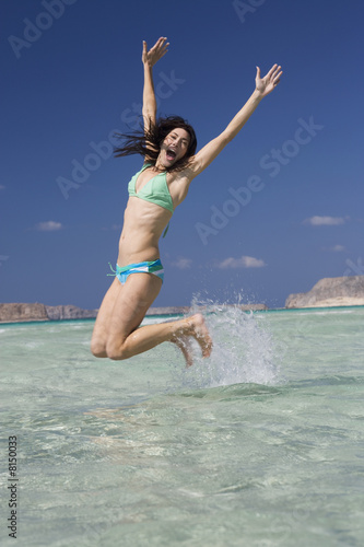 A woman jumping in the sea
