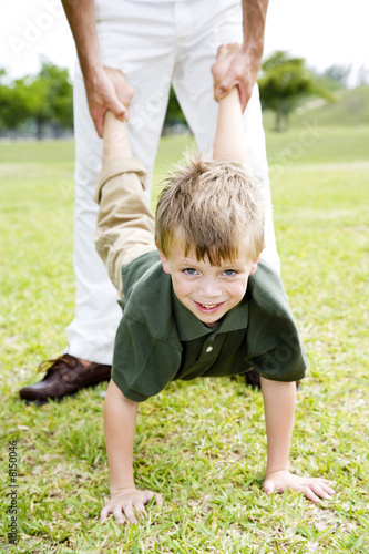 Boy walking on hands father holding legs