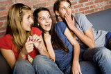 Three teenage girls giggling at something out of shot