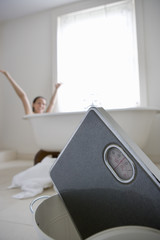 Woman raising arms in bath, bathroom scales in foreground