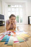 20's woman lying on floor choosing paint colours from paint swatches in living room.