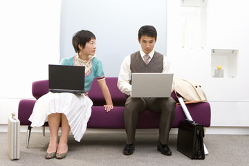Businessman and woman using laptop computers on sofa, woman looking at man, low angle view