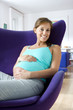 Young pregnant woman in armchair, hands on stomach, smiling, low angle view