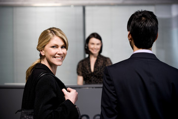 Man and woman arrive at office reception for a business meeting