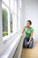 Young woman with paintbrush kneeling on floor, looking at window