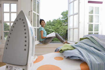 Woman with book on window sill, smiling, portrait, iron on ironing board in foreground (differential focus)