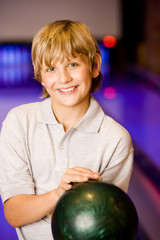 Boy in a bowling alley holding a green bowling ball