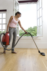 Young woman hoovering by open windows, low angle view