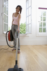 Young woman hoovering by open window, smiling, portrait, low angle angle view