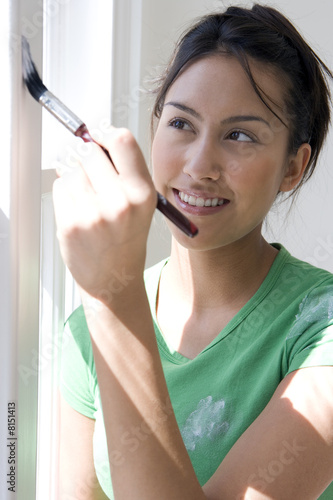 Young woman painting window frame, smiling, close-up