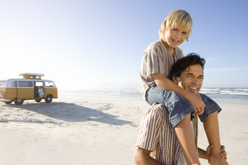 Boy (6-8) on father's shoulders on beach, smiling, portrait