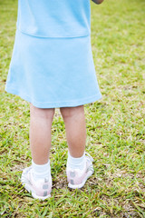 Rear view cropped little girl standing on the grass