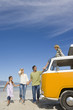 Family of four on beach looking at son (6-8) on roof of camper van