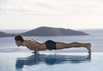 A man exercising by a pool