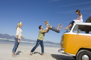 Family of four on beach, father catching son (6-8) jump from roof of camper van, side view
