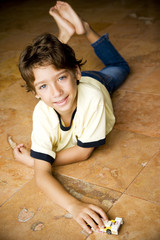 Latino boy playing with toy car on floor