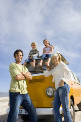 Family of four, parents by son and daughter (5-9) on roof of camper van, smiling, portrait, low angle view