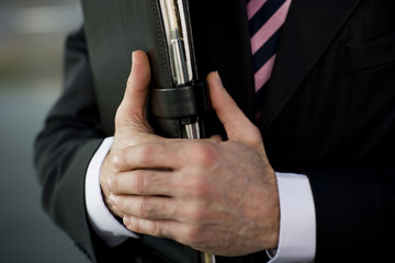 Businessman holding a leather case with briefing papers, close up of hands