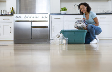 Young woman putting newspaper bundle into recycling bin in kitchen, smiling, portrait, ground view