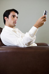 Portrait of a man using a cellphone to SMS text message