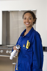 Female plumber with pipes in kitchen, smiling, portrait
