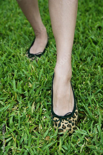 cropped image woman's feet walking on grass