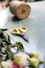 Bunch of roses, scissors and twine in a florist's shop