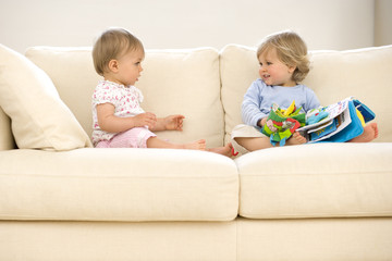 Baby girl (9-12 months) looking at toddler boy (12-15 months) on sofa with toys, side view