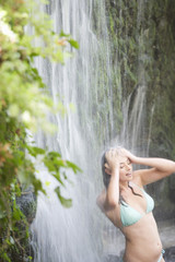 A woman standing in a waterfall
