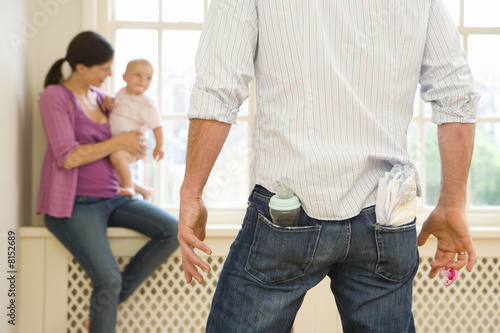 Man with nappies and baby bottle in back pockets looking at pregnant woman with baby daughter (6-9 months), rear view