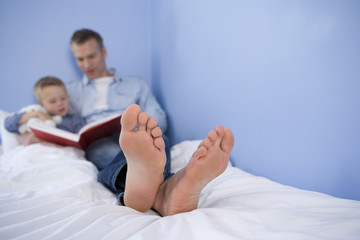 Father reading to son (4-6) in bed, close-up of father's feet (differential focus)