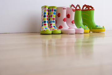 Three pairs of children's coloured rubber boots, ground view