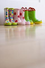 Three pairs of children's rubber boots, ground view
