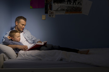 Father reading to son (4-6) in bed, side view (spot lit)