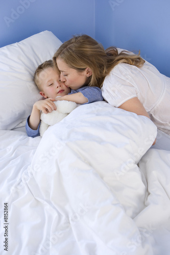 Boy (4-6) asleep in bed, mother kissing cheek, elevated view