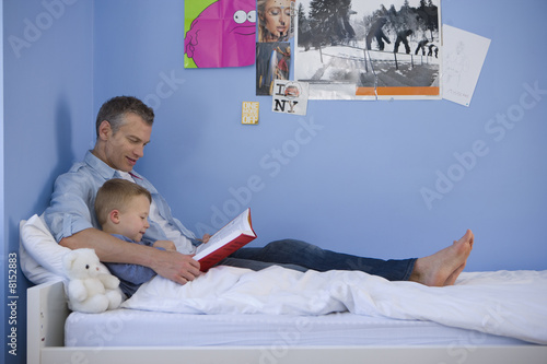 Father reading to son (4-6) in bed, side view