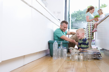 Family of four in kitchen, father and son (2-4) putting recycling into bin, mother and daughter (4-6) with plant in background
