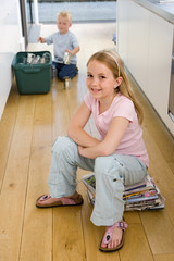 Girl (4-6) on newspaper bundle in kitchen, brother (2-4) putting recycling into bin in background