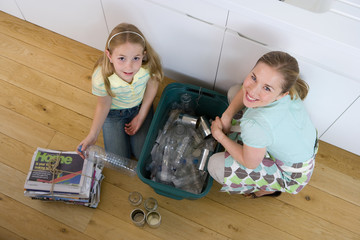 Mother and daughter (4-6) putting recycling into bin in kitchen, smiling, portrait, elevated view