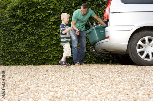 Father and son (4-6) loading recycling into back of car, low angle view