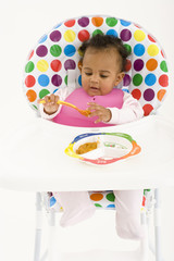 Baby girl (3-6 months) eating in highchair, elevated view