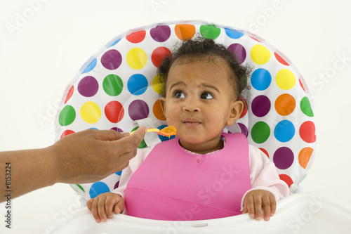 Mother feeding baby girl (3-6 months) in highchair
