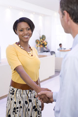 Businesswoman and man shaking hands in foyer, smiling, close-up