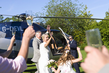 Bride and groom by helicopter waving to wedding guests