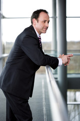 Businessman standing on walkway in office building