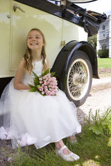 Flower girl (10-12) with bouquet of flowers by vintage car, smiling, low angle view