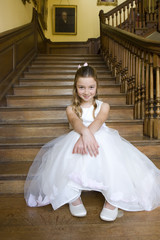 Flower girl (10-12) on stairs, smiling, portrait, low angle view