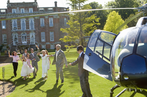 Wedding party waving at bride and groom by helicopter