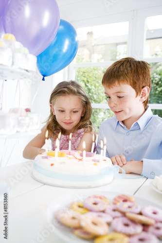 two children sitting at birthday tea table